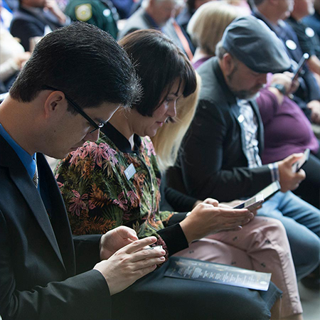 Seated guests interacting with their mobile phones