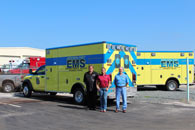 Three men standing next to an EMS van
