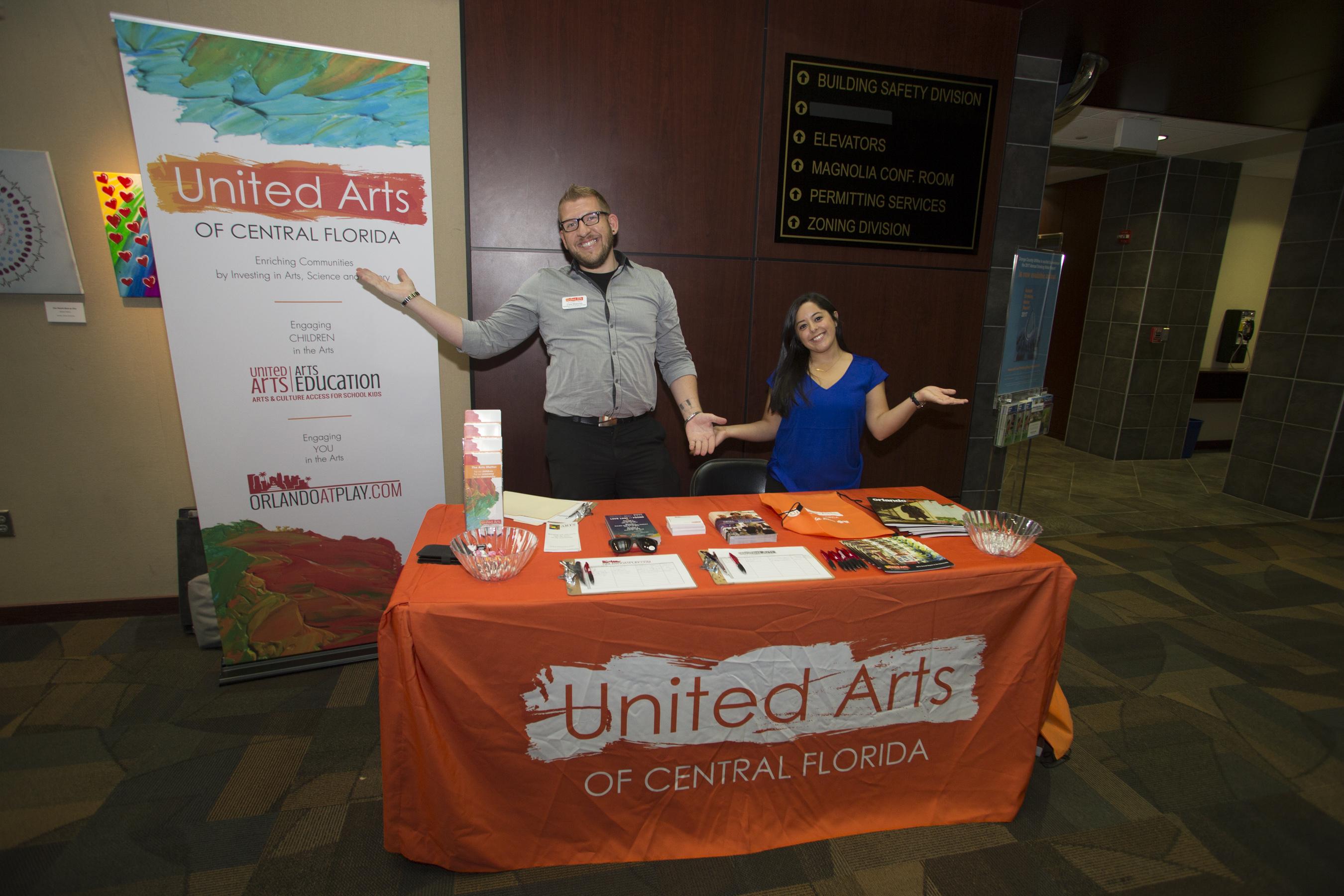Hombre y mujer parados detrás de la mesa donde entregan panfletos en nombre de United Arts of Central Florida