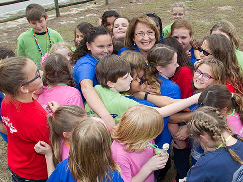 Mayor Teresa Jacobs smiling while being hugged by a dozen children