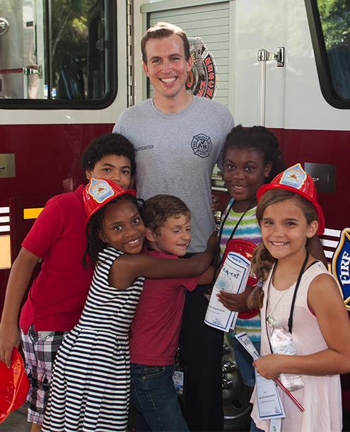 Niños abrazados a un bombero en frente de un camión de bomberos