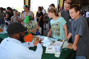 Una familia escucha al personal del Condado de Orange de la División de Protección del Medio Ambientemientras le explica sobre la importancia de la sostenibilidad.