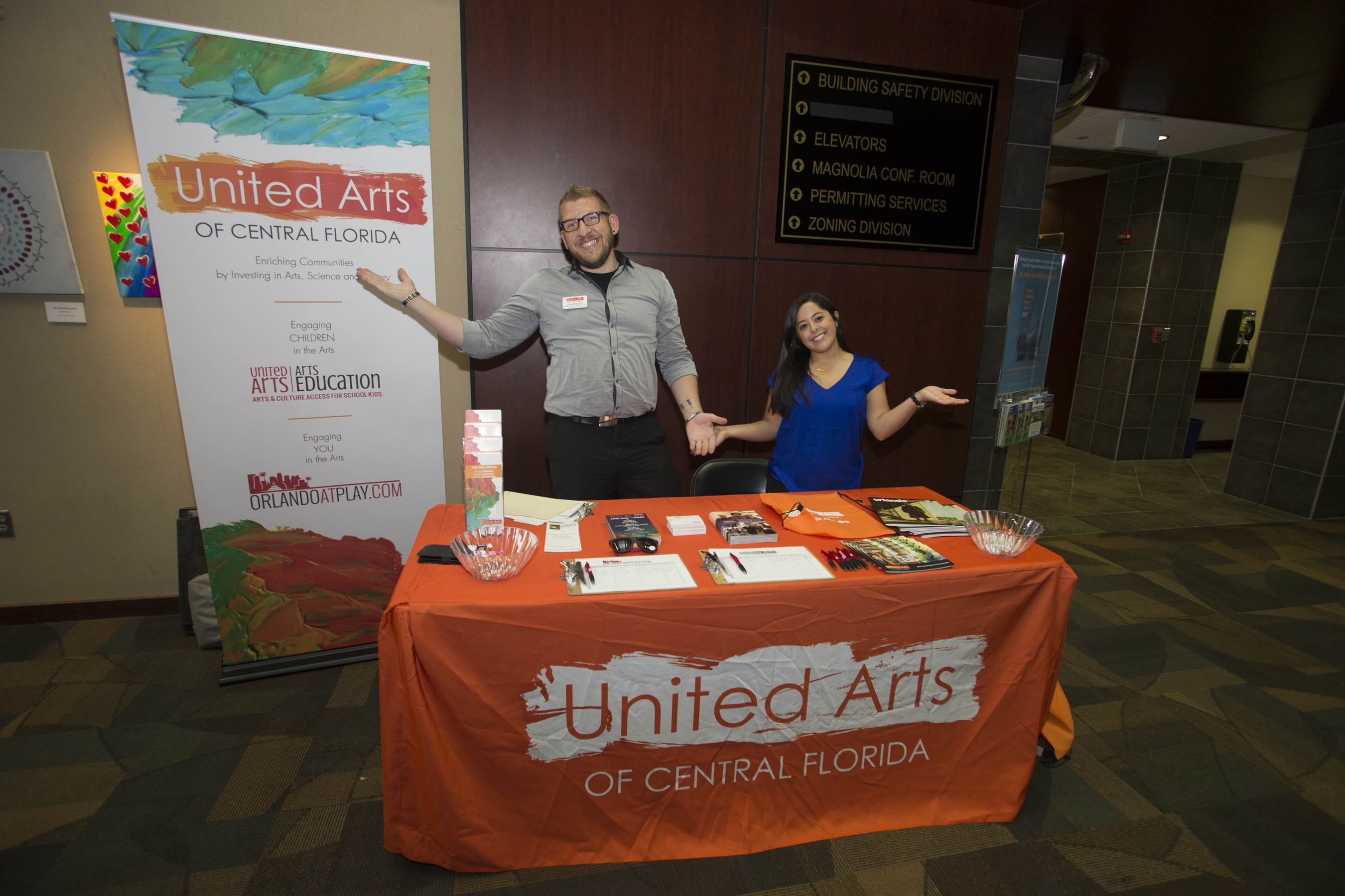 Man and woman standing behind their table where they are handing out pamphlets on behalf of United Arts of Central Florida
