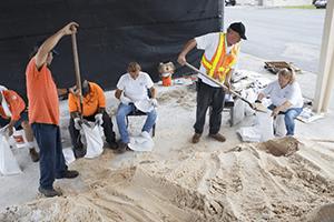 Personas llenando bolsas de arena