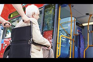 Hombre mayor en silla de ruedas recibe ayuda para subir a un transporte